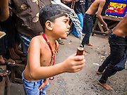 04 NOVEMBER 2014 - YANGON, MYANMAR: A Burmese boy flagellates himself with chains and razors in front of Mogul Mosque (Masjid) on Ashura in Yangon. The flagellation shows solidarity with Hussein and his family. Mogul Mosque is the principal Shia mosque in Yangon. Ashura commemorates the death of Hussein ibn Ali, the grandson of the Prophet Muhammed, in the 7th century. Hussein ibn Ali is considered by Shia Muslims to be the third imam and the rightful successor of Muhammed. He was killed at the Battle of Karbala in 610 CE on the 10th day of Muharram, the first month of the Islamic calendar. According to Myanmar government statistics, only about 4% of the population is Muslim. Many Muslims have fled Myanmar in recent years because of violence directed against Burmese Muslims by Buddhist nationalists.     PHOTO BY JACK KURTZ