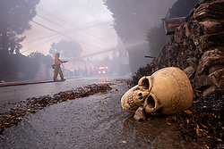 October 28, 2019, Los Angeles, California, USA: Firefighters put water on a burning home along Trailridge in Los Angeles in the Getty fire Monday. A Halloween decoration is seen in the foreground (Credit Image: © David Crane/Orange County Register via ZUMA Wire)