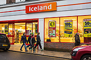 Four British children walk past a large and bright Iceland supermarket in Blandford Forum, United Kingdom.  Iceland is a British supermarket chain in the United Kingdom and Ireland.  Its primary product lines are frozen foods, such as ready meals and potato chips.