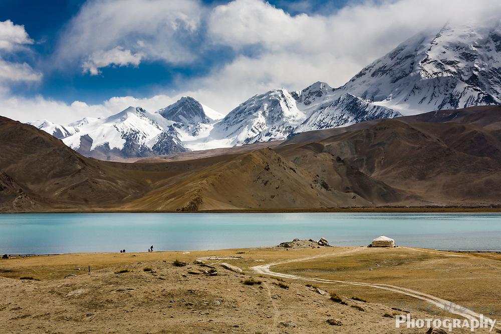 Stunning blue Lake Karakul with Tajik ger tent house, Himalayas