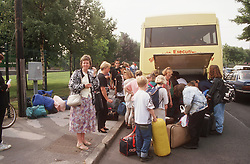 Secondary school pupils loading luggage into coach in preparation for school trip,