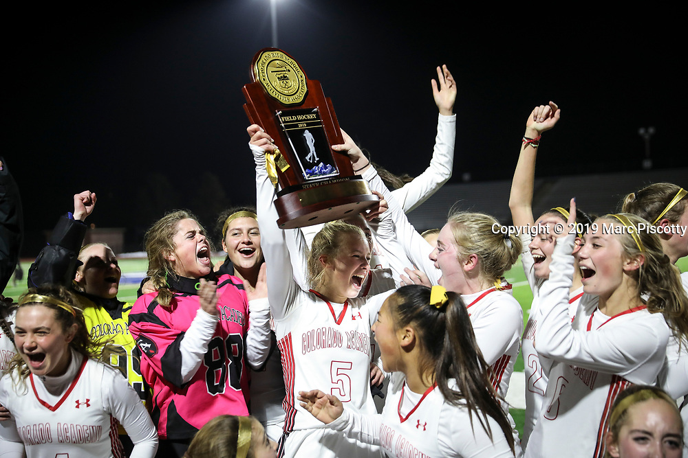 SHOT 11/5/19 8:25:00 PM - Colorado Academy field hockey teammates celebrate as they're presented the 2019 CHSAA State Field Hockey Tournament Championship trophy at All-City Stadium Tuesday evening. Colorado Academy won the game 2-1 over Regis Jesuit to earn the state title. (Photo by Marc Piscotty / © 2019)