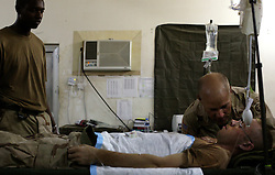 Chaplain Timothy Smith prays over Spc. Timothy McVay, Baghdad, Iraq, Aug. 10, 2003.<br />Members of Company C, 407th Forward Support Battalion, 82nd Airborne Division, known as the Charlie Med treated McVay who was injured when a piece of shrapnel punctured his arm after an Improvised Explosive Device exploded while on patrol.