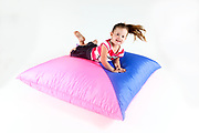Indoor playground  Girl bounces on a cushion On white Background