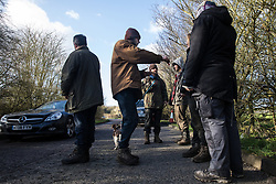 Denham, UK. 11 February, 2020. Environmental activists from Extinction Rebellion, Stop HS2 and Save the Colne Valley 'slow walk' in front of a large truck transporting a JCB forklift truck to a HS2 site at Denham in the Colne Valley. Local traffic passes on the other side of the road. Contractors working on behalf of HS2 are rerouting electricity pylons through a Site of Metropolitan Importance for Nature Conservation (SMI) in conjunction with the high-speed rail link.