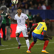 DeAndre Yedlin, (left), USA, passes the ball past Walter Ayoví, Ecuador, during the USA Vs Ecuador International match at Rentschler Field, Hartford, Connecticut. USA. 10th October 2014. Photo Tim Clayton