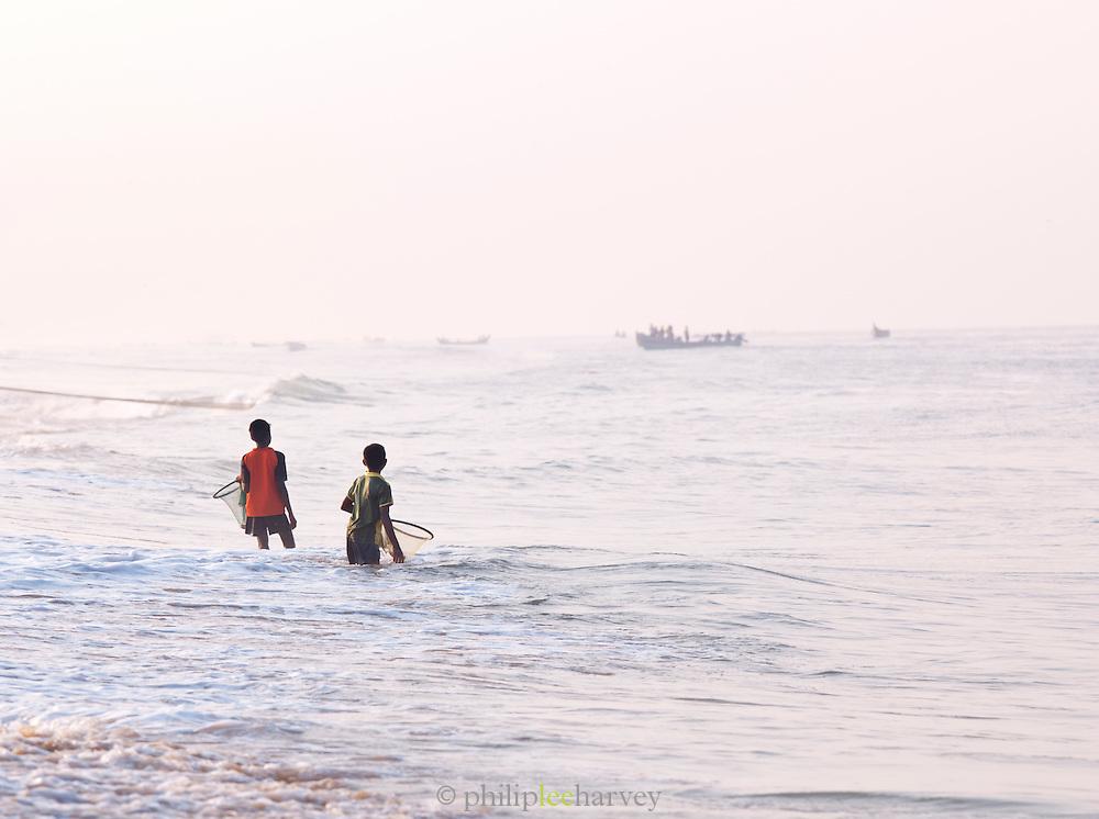 Boys with fishing nets on the busy fishing area at Poovar Beach, near Trivandrum (Thiruvananthapuram), Kerala, India