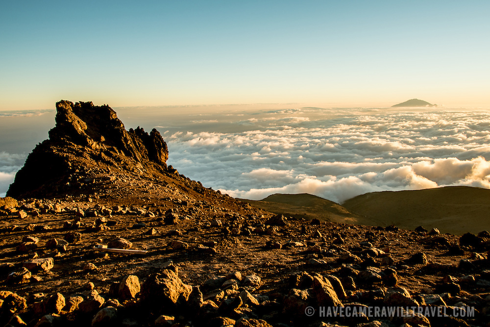 The summit of Mt Meru pokes through the clouds as seen from Arrow Glacier on Mt Kilimanjaro's Lemosho Route.