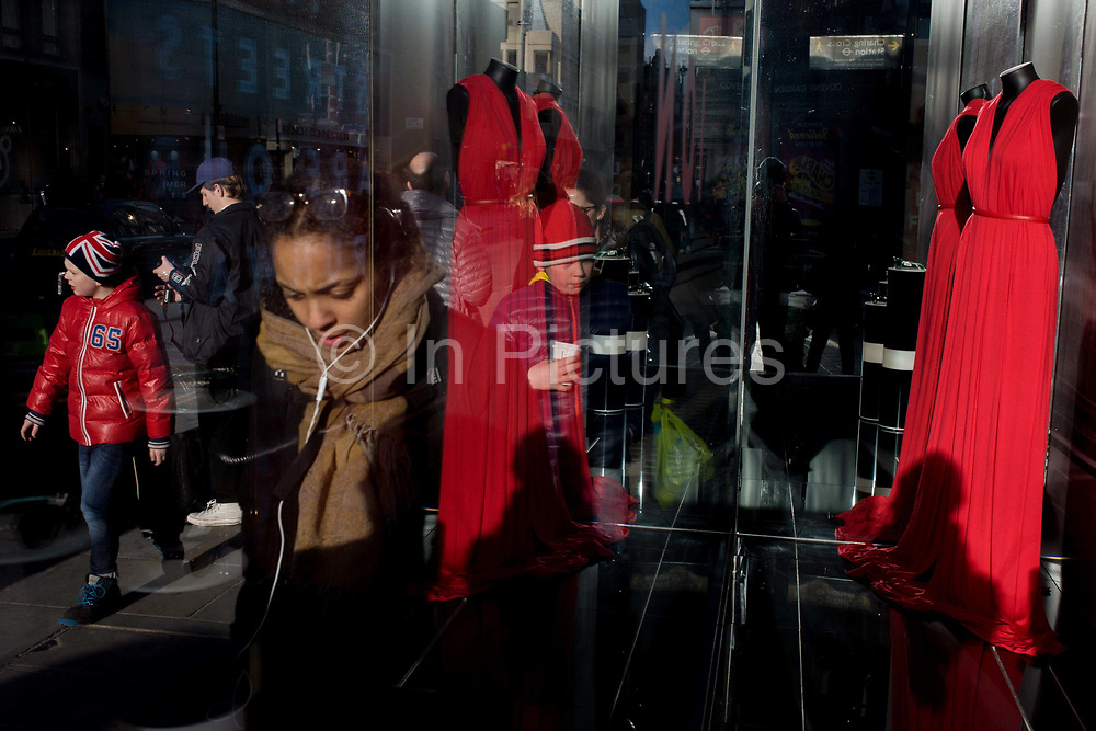 Passers-by and London Fashion Week red dress in central London window. The red frock stands in the window of a Covent Garden shop selling sunglasses but who champion the bi-annual style and fashion fest around the capital. Passers-by walk past the window in strong afternoon winter sunshine.