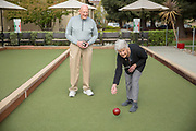 A senior women playing bocce ball with her friend.