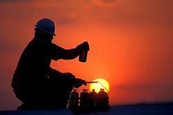 Oil industry worker holds up sample bottle into the light of the setting sun.