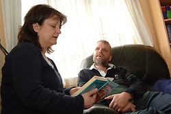 A visually impaired and brain damaged man has a story read to him by carer