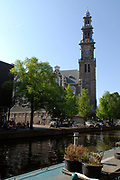 """The Westerkerk (""""western church"""") is a Protestant church in Amsterdam, built in 1620-1631 after a design by Hendrick de Keyser. The church is in Amsterdam's Jordaan district, at the bank of the Prinsengracht canal.<br /> <br /> The spire is the highest church tower in Amsterdam, at 85 meters (279 feet). The crown topping the spire is the Emperor's Crown of Maximilian I. The church bells were made by the brothers Hemony.<br /> <br /> Rembrandt van Rijn was buried in the Westerkerk on October 8, 1669. The exact location of the grave is unknown, but presumed to be somewhere along the northern wall. Rembrandt's lover Hendrickje Stoffels is also buried here, and his son Titus van Rijn may also be. Other painters buried in the Westerkerk are Nicolaes Berchem, Gillis d'Hondecoeter, Melchior d'Hondecoeter and Govert Flinck. The church organ is decorated with doors painted by Gerard de Lairesse.<br /> <br /> The Westerkerk is located close to the Achterhuis (now Anne Frank House)"""