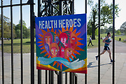 As the UK government's lockdown restrictions during the Coronavirus pandemic continues, and number of UK reported cases rose to 138,078 with a total now of 18,738 deaths, a runner passes behind a home-made piece of art celebrating NHS (National Health Service) care worker heroes <br /> attached to the gates of Brockwell Park, a public green space in the south London borough of Lambeth, on 23rd April 2020, in London, England.