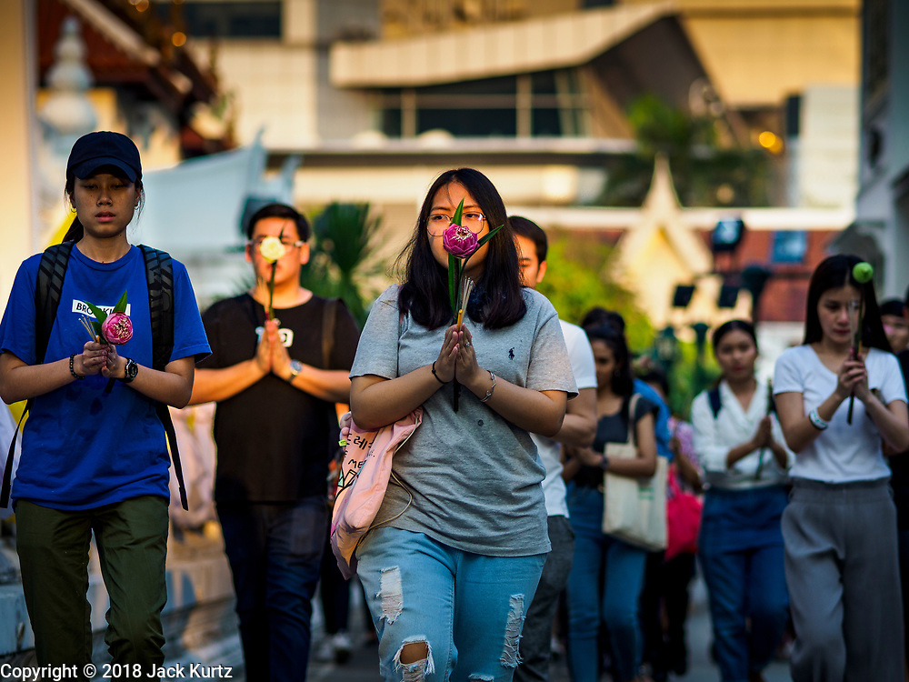 """01 MARCH 2018 - BANGKOK, THAILAND:    People participate in a procession around at Wat Pathum Wanaram in central Bangkok. Many people go to temples to perform merit-making activities on Makha Bucha Day, which marks four important events in Buddhism: 1,250 disciples came to see the Buddha without being summoned, all of them were Arhantas, or Enlightened Ones, and all were ordained by the Buddha himself. The Buddha gave those Arhantas the principles of Buddhism. In Thailand, this teaching has been dubbed the """"Heart of Buddhism.""""    PHOTO BY JACK KURTZ"""
