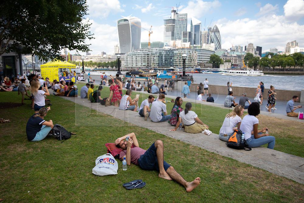 © Licensed to London News Pictures. 24/07/2018. London, UK. Workers and tourists enjoy the hot weather around London Bridge at lunchtime today. Temperatures in the South East of the UK are reaching over 30 degrees celsius today, following the hottest day of the year yesterday. Photo credit : Tom Nicholson/LNP