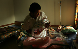 "Ali Salah Tambre, 28, hold Inas, his newborn daughter, while mother Jawaher Ali Salah, 19, looks on, inside the Shepherd's Field Hospital in Bethlehem, Palestinian Territories, Nov. 15, 2004. The baby was born via cesarian section when she was breeched. Once the baby goes home and the family has gathered enough money, they will slaughter one sheep. When a boy is born, two sheep are killed in celebration. ""We are very poor, so all we can do right now is give sweets to our neighbors,"" said the father Ali. He used to work as a laborer in Israel but has been unemployed since the beginning of the Second Intifada."