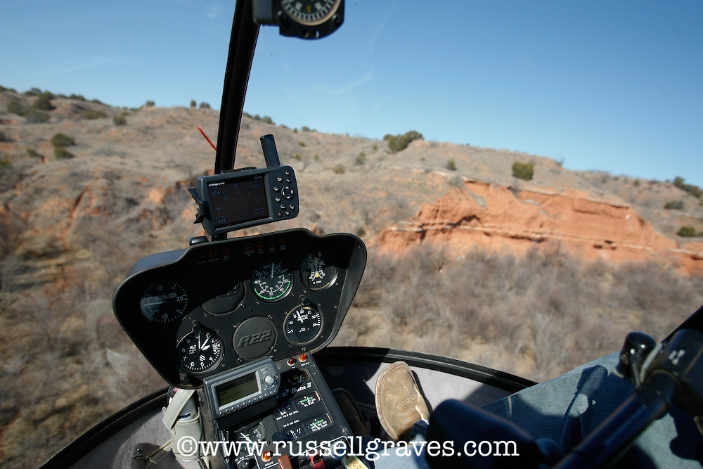 HELICOPTER FLYING ACROSS TEXAS RANGELANDS ON A FERAL HOG ERADICATION PROJECT