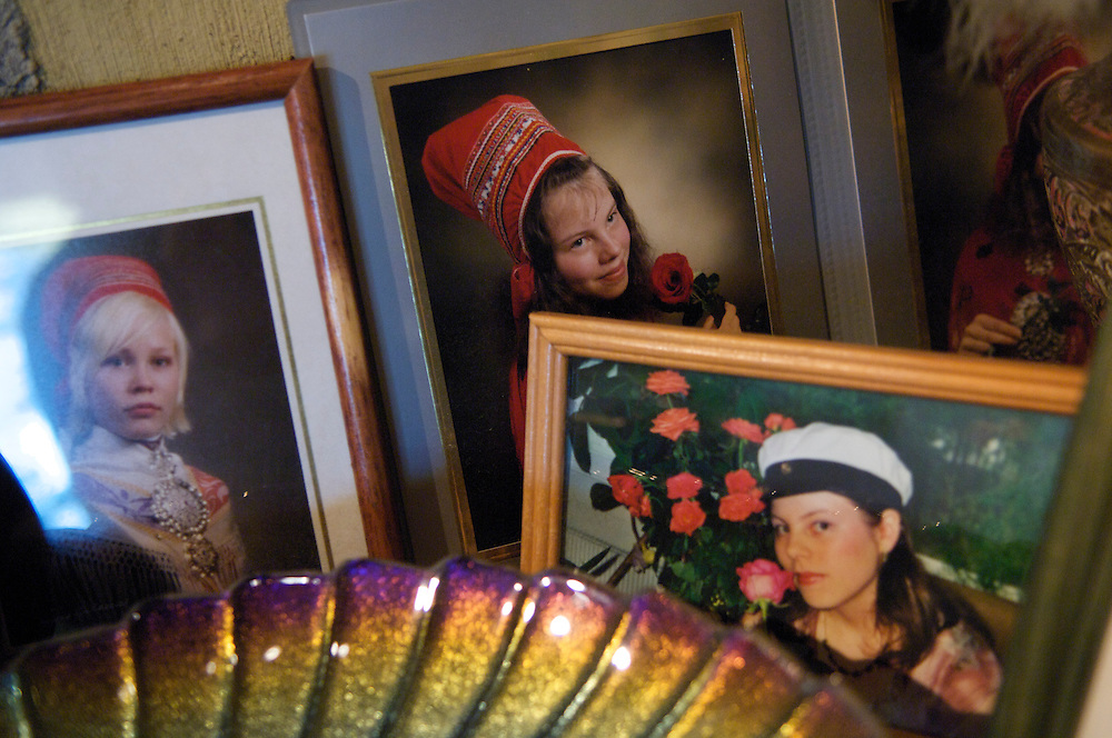 Family pictures of Sami youth dressed in traditional clothing are arranged in the living room of herdsman Veggai's house.  At the present time, many Sami work outside of traditional jobs and pursue a variety of occupations, yet reindeer herding remains an integral part of Sami life.  The Sami herding lifestyle struggles to maintain its force in numbers with lower wages and a demanding work schedule. Very few youth seek a future as a full time herder.
