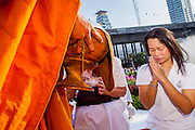 20 OCTOBER 2012 - BANGKOK, THAILAND: A woman bows her head in prayer after making a donation to a Buddhist monk during an alms giving ceremony in Bangkok. More than 2,600 Buddhist Monks from across Bangkok and thousands of devout Thai Buddhists attended the mass alms giving ceremony in Benjasiri Park in Bangkok Saturday morning. The ceremony was to raise food and cash donations for Buddhist temples in Thailand's violence plagued southern provinces. Because of an ongoing long running insurgency by Muslim separatists many Buddhist monks in Pattani, Narathiwat and Yala, Thailand's three Muslim majority provinces, can't leave their temples without military escorts. Monks have been targeted by Muslim extremists because, in the view of the extremists, they represent the Thai state.        PHOTO BY JACK KURTZ