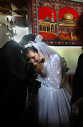 KABUL,AFGHANISTAN - AUGUST 29: An Afghan bride cries and kisses a relative goodbye at the end of her wedding ceremony inside a hotel, August 30, 2002 in Kabul, Afghanistan. Each Friday, every beauty salon is filled with  brides, the hotels are jammed with young couples and most streets are packed with streams of cars, blaring their horns as Afghans rush to get married after decades of war. (Photo by Ami Vitale/Getty Images)