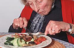 Elderly woman eating meal,