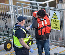 © Licensed to London News Pictures. 31/03/2021. Dover, UK. A migrant is helped ashore by a Border Force officer at Dover Harbour in Kent after crossing the English Channel. Home Secretary Priti Patel has pledged an overhaul of asylum seeker rules, with refugees having their claim assessed based on how they arrive in the UK. Photo credit: Stuart Brock/LNP
