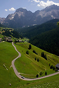 Winding rural road and traffic in Dolomites near La Val in Alta Badia, south Tyrol, Italy. We look across the farms and alpine homes linked by narrow but well-maintained roads high up with the stunning panoramic scenery of mountain peaks. According to the 2011 census, there are 505,000 inhabitants in south Tyrol with an area of 7,400 sq Km with 60% over 1,600m above sea level. La Val (German: Wengen; Italian: La Valle) is a comune (municipality) in the province of South Tyrol in northern Italy, located about 45 kilometres (28 mi) northeast of the city of Bolzano.