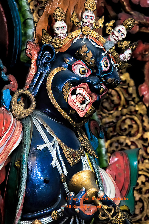 Happy Skulls: Happy skulls form a crown on this prominent blue statue in the main temple of the Mak Dhog Monastery Aloobar, Darjeeling India.