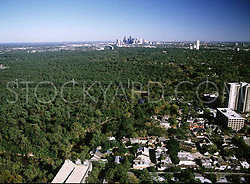 Aerial view of the downtown Houston, Texas skyline across a vast canopy of trees.