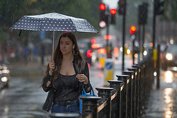 © Licensed to London News Pictures.  25/07/2021. London, UK. A woman makes her way along the Euston Road which has flooded in central London as thunderstorms and heavy rainfall hit parts of London.  Photo credit: Marcin Nowak/LNP