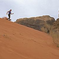Lisa Gnade (MR) runs down dune below Rakabat Canyon on Jebel Um Ishrin in the Wadi Rum, Jordan.