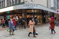 © Licensed to London News Pictures. 12/12/2020. London, UK. Shoppers walk past John Lewis department store in Oxford Street on a busy Saturday afternoon. London is currently under Tier 2 Covid restrictions and could be facing Tier 3 as the Covid-19 case rate has been the highest in the UK. Photo credit: Ray Tang/LNP
