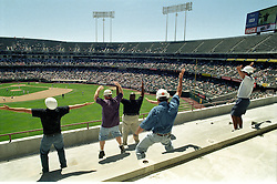 """Oakland Alameda County Coliseum: Construction workers do a """"Y.M.C.A."""" dance in the left field stands between inning of the Oakland Athletics game. The Coliseum was under going expansion construction for the return of the Oakland Raiders. The A's started the 1996 season in Las Vegas for a few games while the stadium construction was finished..The A's opened in Las Vegas."""