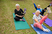 A group of senior women stretching on yoga mats outside being playful.
