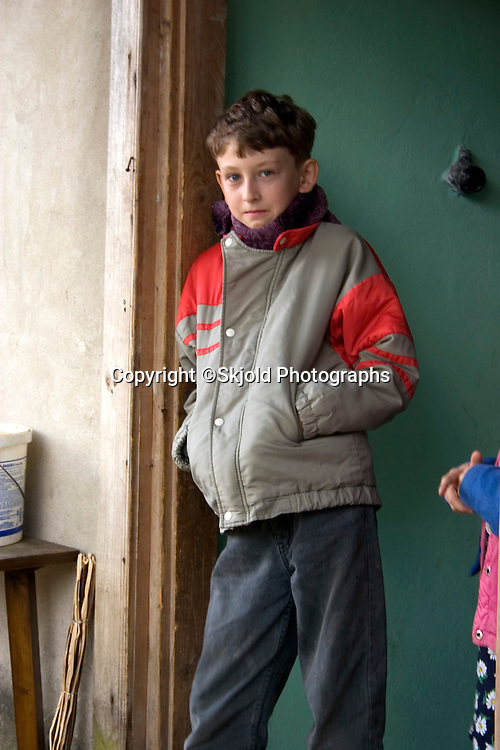 Polish farmer's son waiting in the doorway on his way to school. Zawady Central Poland
