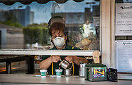 Wearing a protective mask Nina Porras serves a Colada at La Ventanita outside the popular Versailles Cuban restaurant now open for take out service only during the COVID19 pandemic in Miami on Wednesday, April 1, 2020.