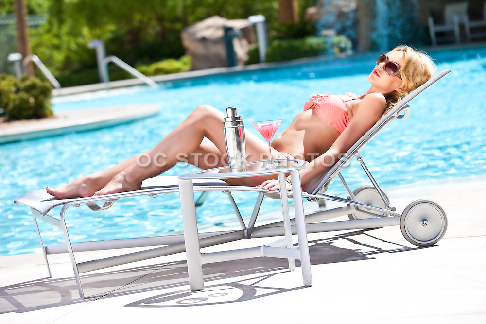 Sexy Blonde Female Lounging At The Pool  With A Martini