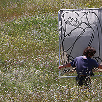 UC Santa Cruz senior Chloe Murr carries one of her paintings through the Great Meadow on campus to photograph the piece. Murr is one of 13 undergraduate UCSC students who are being recognized for excellence in the arts by the 2020 Irwin Scholarships. Recipients of the award are included in group show each year. With our current pandemic reality and the closing of the UCSC campus, this year the work will be displayed digitally in IRWIN 2020: Collective Solitude, the 34th annual Irwin Scholarship Award exhibition. The students were tasked to create work in a period of heightened uncertainty and separation as artists worldwide are tasked with finding creative ways to bridge the gaps between people. The were asked how, as artists, they can work under such great limitations to maintain communities and a sense of togetherness?  Murr is joined in the show by Aaron Martinez, Anastasia Oleson, Angel Gonzales, Dominic Ramirez, Edgar Cruz, Emma McWaid, Jocelyn Lee, Joshua Zupan, Morgan Tomfohr, Natalie Del Castillo, Rodrigo Ramos, and Veriche Blackwell.  As a way of ensuring that others would have the kind of art education that allowed her to flourish in the art community, the late Sue Irwin established the William Hyde and Susan Benteen Irwin Scholarship Fund in 1986 in honor of her husband. The show runs June 3 through June 30 and will be available online for viewing at: art.ucsc.edu/sesnon/irwin-2020  (Shmuel Thaler — Santa Cruz Sentinel)