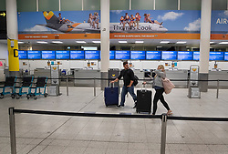 © Licensed to London News Pictures. 23/09/2019. Gatwick, UK. Passengers walk past closed Thomas Cook check-in desks at Gatwick Airport after the travel firm collapsed overnight. The 178 year old travel operator has gone in to liquidation after rescue talks failed overnight. This will trigger the largest peacetime repatriation as more than 150,000 British holidaymakers will need to be brought home. Photo credit: Peter Macdiarmid/LNP