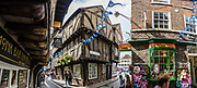 """The charming Shambles is one of the best preserved medieval streets in the world, and sits amid a district of twisting, narrow streets in York, England, United Kingdom, Europe. The Shambles was mentioned in the Doomsday Book of William the Conqueror in 1086. Many of its buildings date from 1350-1475, when the street hosted butchers' shops and houses. The overhanging timber-framed fronts of the Tudor buildings shelter the """"wattle and daub"""" walls below and would keep direct sunshine off of the butchers' meat. """"Shambles"""" may derive from """"Shammel,"""" an Anglo-Saxon word for the slaughterhouse shelves of the open shop-fronts. This image was stitched from multiple overlapping photos."""