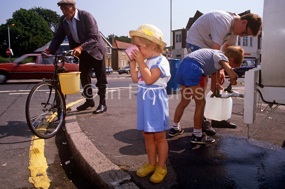 As the community fill up their water butts and buckets, a young girl drinks fresh water from a cup supplied by a water tanker, provided by Thames Water during the southern England drought of 1989. During the heatwave that saw reservoirs depleted and in the south west, dry up altogether. A hosepipe ban and in some areas, tap water failed too so tankers stationed in affected areas so locals could fill up for essential use. Tourism increased as people visited tourist areas e.g. beaches at the weekends and took holidays in the UK rather than travelling abroad for the sun
