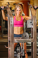 Physically fit woman on a pullup machine in a healthclub.