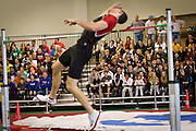 A high jumper leaps over the bar as the full-capacity stands are seen in the background of the Bear Recreation and Athletic Center Field House.