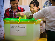 08 NOVEMBER 2015 - YANGON, MYANMAR:   A woman drops her completed ballot into the ballot box in central Yangon. The citizens of Myanmar went to the polls Sunday to vote in the most democratic elections since 1990. The National League for Democracy, (NLD) the party of Aung San Suu Kyi is widely expected to get the most votes in the election, but it is not certain if they will get enough votes to secure an outright victory. The polls opened at 6AM. In Yangon, some voters started lining up at 4AM and lines were reported to long in many polling stations in Myanmar's largest city.    PHOTO BY JACK KURTZ