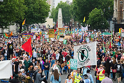 London, June 20th 2015. Thousands of people converge on the streets of London to join the People's Assembly Against Austerity's march from the Bank of England to Parliament Square. PICTURED: With Parliament Square completely packed with humanity, protesters listen to and watch rally speakers relayed to them on a giant screen in Whitehall.