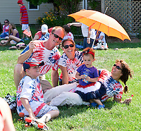 Bob Page, Erica Duncan, Ayden Duncan, Addison Duncan and Janice Page from the Skate Escape crew gather under an umbrella for some shade following the annual July 4th parade Monday afternoon.  (Karen Bobotas/for the Laconia Daily Sun)