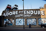 Graffiti in Shoreditch asks us 'Let's adore and endure each other' as a couple walk past. This area is famed for it's creative, beautiful and poetic graffiti street art. Two disused tube train carriages sit atop what was one the old railway bridge.