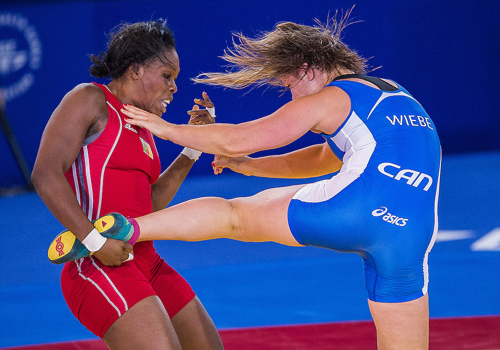 July 29, 2014: Erica Wiebe of Canada (Blue) takes on Annabel Ali (Red) of Cameroon in the Women's 75kg Nordic Wrestling competition at the Scottish Exhibition Conference Centre during the XX Commonwealth Games in Glasgow, Scotland.