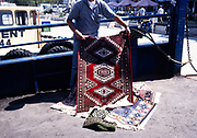 Street seller displaying Turkish rug for sale at Cannakale, Turkey in 1997